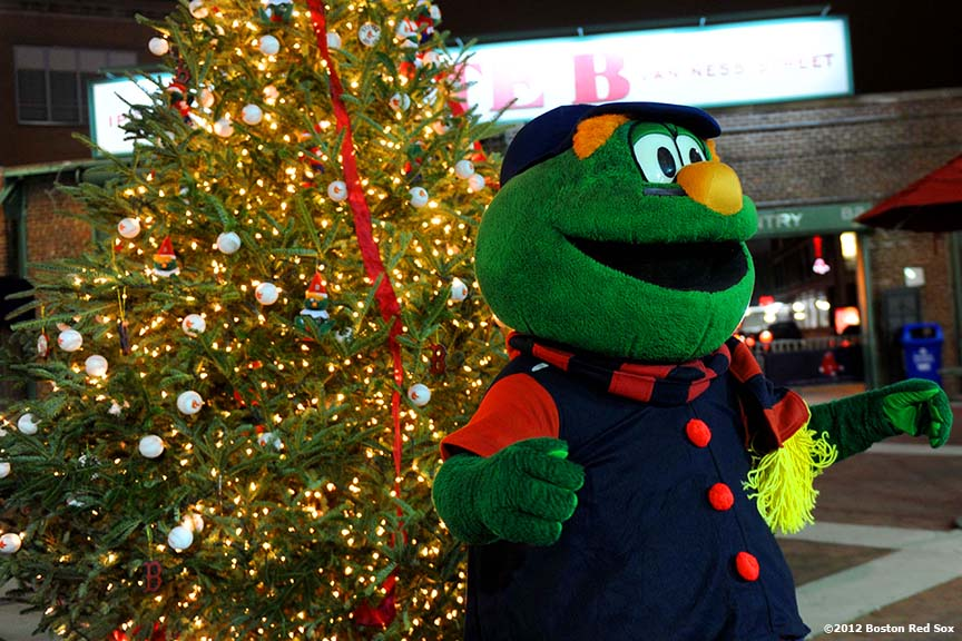"""Wally the Green Monster poses for photographs during Fenway Park Holiday Bash Friday, November 30, 2012. The event featured player and alumni meet and greets, a Fenway Winter Village set up in the Big Concourse, access for fans to the home clubhouse and warning track, and an LED Winter Lights musical projected on the Green Monster."""