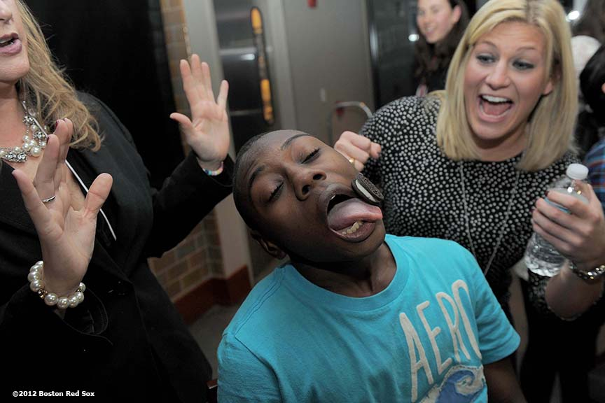 """A member of the 2012 class of Boston Red Sox scholars attempts to move an Oreo cookie from her forehead to her mouth without using her hands at Fenway Park Friday, December 14, 2012. The 'cookie drop' was one of several games at the scholars holiday party."""