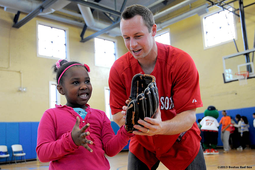 """Boston Red Sox outfielder Daniel Nava gives fielding advice to Treasure Blackwell, 6, at the Vine Street Community Center in Roxbury, MA. Nava, along with Red Sox pitcher Andrew Bailey and Wally the Green Monster, visited the center to run baseball clinics, answer questions, and pose for photographs."""