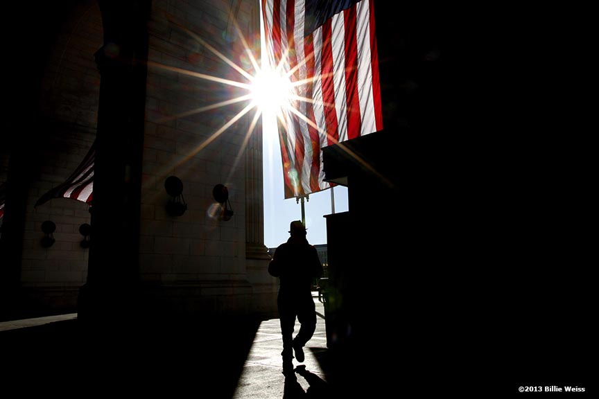 """he sun rises as a pedestrian passes by the entrance of Union Station in Washington, D.C. on the day before the 57th Presidential Inauguration Sunday, January 20, 2013."""