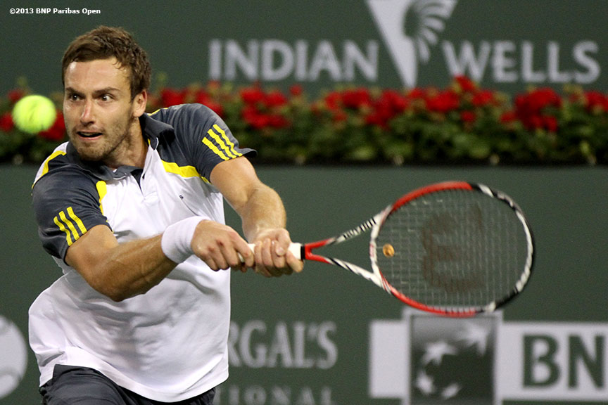 """Ernests Gulbis returns a shot during his match against Rafael Nadal Wednesday, March 13, 2013 at the BNP Paribas Open in Indian Wells, California."""