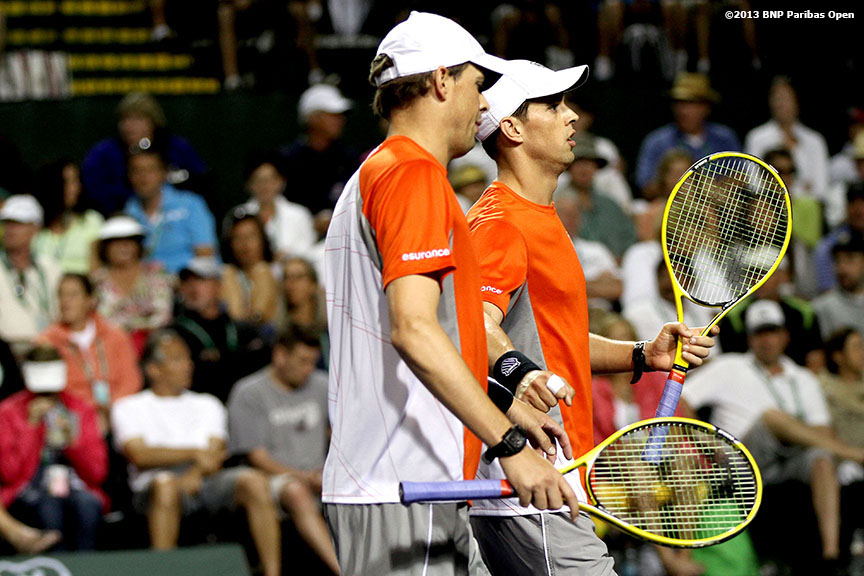 """Bob and Mike Bryan talk between points during their match against John Isner and Same Querrey Monday, March 11, 2013 at the BNP Paribas Open in Indian Wells, California."""