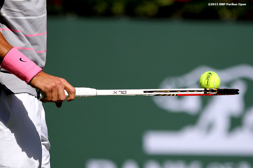 """Grigor Dimitrov balances tennis balls on his racquet during his match against Novak Djokovic Tuesday, March 12, 2013 at the BNP Paribas Open in Indian Wells, California."""