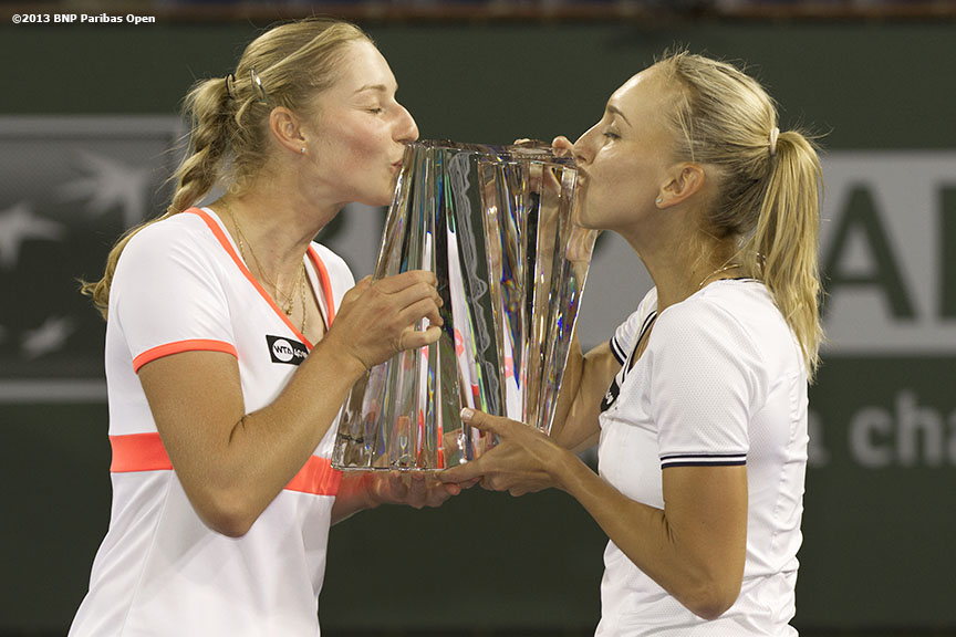 """Ekaterina Makarova and Elena Vesnina kiss the trophy after winning the women's doubles championship Saturday, March 16, 2013 at the BNP Paribas Open in Indian Wells, California."""