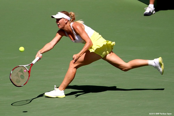 """Caroline Wozniacki lunges for a backhand during the BNP Paribas Open championship match against Maria Sharapova Sunday, March 18, 2013 in Indian Wells, California."""