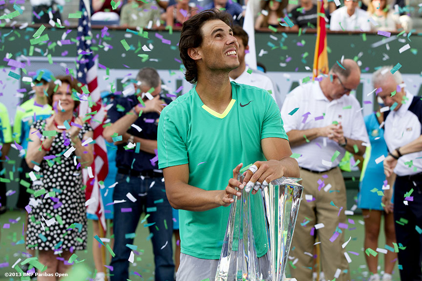 """Confetti falls as Rafael Nadal poses with the championship trophy after defeating Juan Martin Del Potro Sunday, March 18, 2013 at the BNP Paribas Open in Indian Wells, California."""