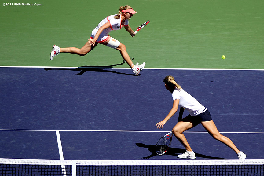 """Ekaterina Makarova lunges for a shot alongside Elena Vesnina during their doubles match against Casey Dellacqua and Kimika Date-Krumm Thursday, March 14, 2013 at the BNP Paribas Open in Indian Wells, California."""