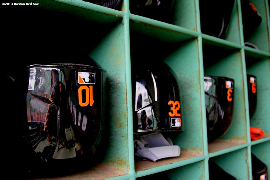 """""""Batting helmets are lined up inside the Baltimore Orioles dugout at Fenway Park before the Boston Red Sox 2013 home opener Monday, April 9, 2013."""""""