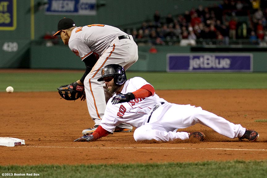 """Boston Red Sox second baseman Dustin Pedroia slides into third base during the third inning of a game against the Baltimore Orioles Thursday, April 11, 2013 at Fenway Park in Boston, Massachusetts."""