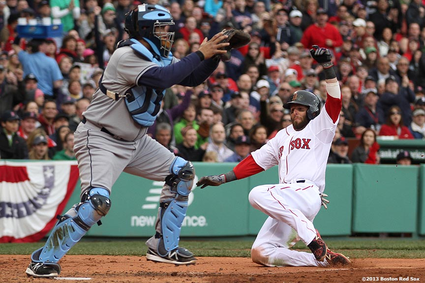 """Boston Red Sox second baseman Dustin Pedroia slides into home during the third inning of a game against the Tampa Bay Rays Sunday, April 14, 2013 at Fenway Park in Boston, Massachusetts."""