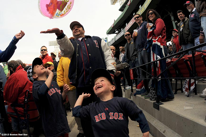 """A young fan hits a beach ball during a game between the Boston Red Sox and the Tampa Bay Rays Monday, April 15, 2013 at Fenway Park in Boston, Massachusetts."""