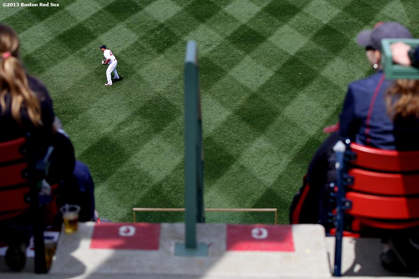 """Shane Victorino is shown in the outfield grass during a game between the Boston Red Sox and the Tampa Bay Rays Monday, April 15, 2013 at Fenway Park in Boston, Massachusetts."""