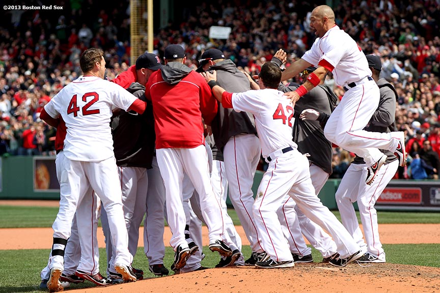 """Boston Red Sox outfielder Shane Victorino jumps into a pile of players as they celebrate after walk-off RBI double by first baseman Mike Napoli to defeat the Tampa Bay Rays 3-2 in the bottom of the ninth inning Monday, April 15, 2013 at Fenway Park in Boston, Massachusetts."""