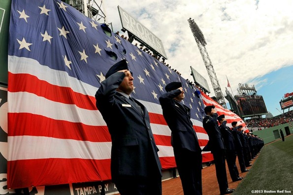 """An American flag drops over the Green Monster at Fenway Park in Boston, Massachusetts Monday, April 15, 2013 during a pre-game ceremony recognizing Patriot's Day."""