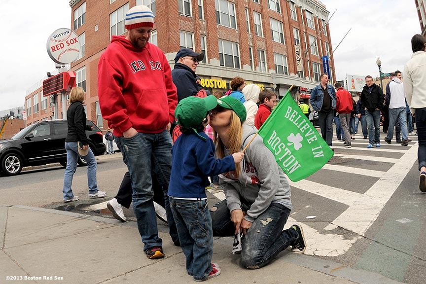 """Shawna Salomon of Auburn, Massachusetts kisses her son, Jacob, 3, as Blake Ratcliffe of Brighton, Massachusetts watches on Yawkey Way during the first Boston Red Sox home game after the attacks on the 2013 Boston Marathon Saturday, April 20, 2013."""