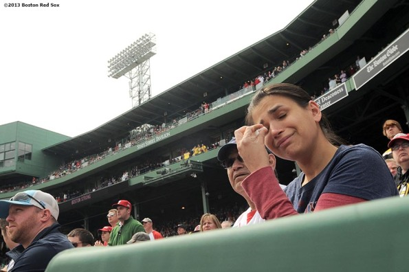 """A fan wipes tears away during a pre-game ceremony honoring the victims, first responders, and others involved in the attacks on the 2013 Boston Marathon Saturday, April 20, 2013."""