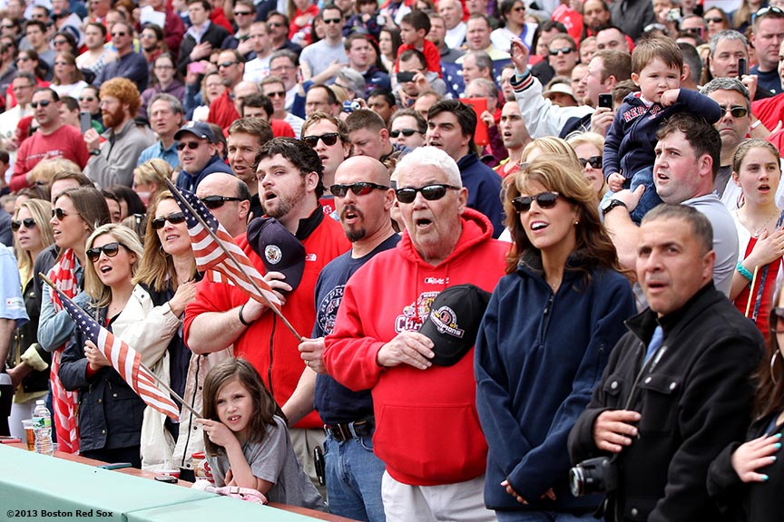 """Fans sing along to the National Anthem during a pre-game ceremony honoring the victims, first responders, and others involved in the attacks on the 2013 Boston Marathon Saturday, April 20, 2013."""