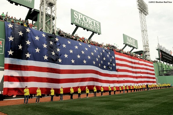 """Marathon Volunteers stand in front of the American Flag on the Green Monster during a pre-game ceremony honoring the victims, first responders, and others involved in the attacks on the 2013 Boston Marathon Saturday, April 20, 2013."""