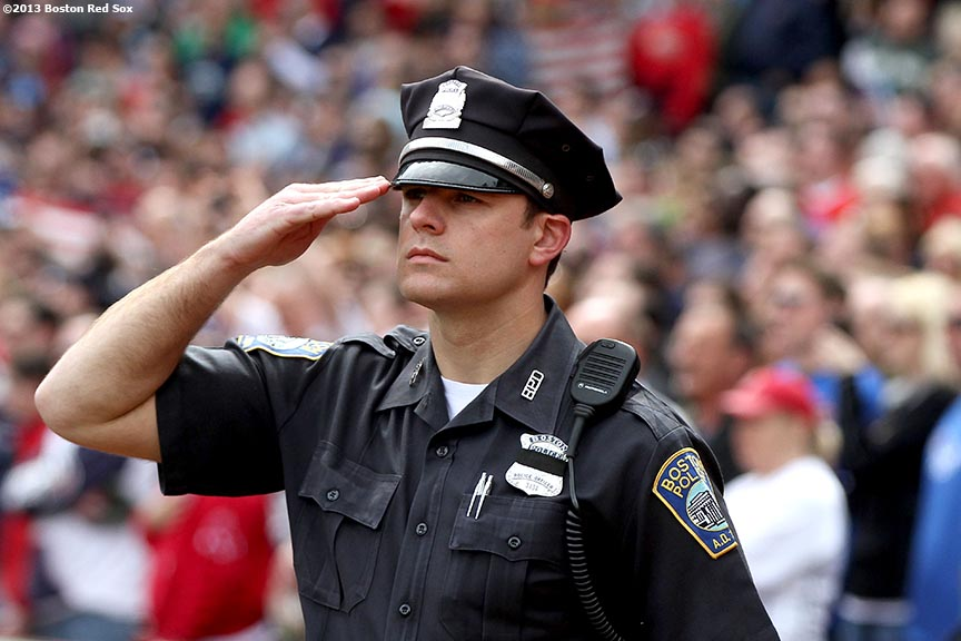 """A Boston Police Officer salutes the flag during a pre-game ceremony honoring the victims, first responders, and others involved in the attacks on the 2013 Boston Marathon Saturday, April 20, 2013."""