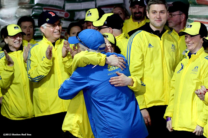 """Marathon Volunteer Tinamarie Sanborn of Somerville, Massachusetts gives a birthday hug to Tom Licciardello of North Andover, Massachusetts during a pre-game ceremony honoring the victims, first responders, and others involved in the attacks on the 2013 Boston Marathon Saturday, April 20, 2013."""