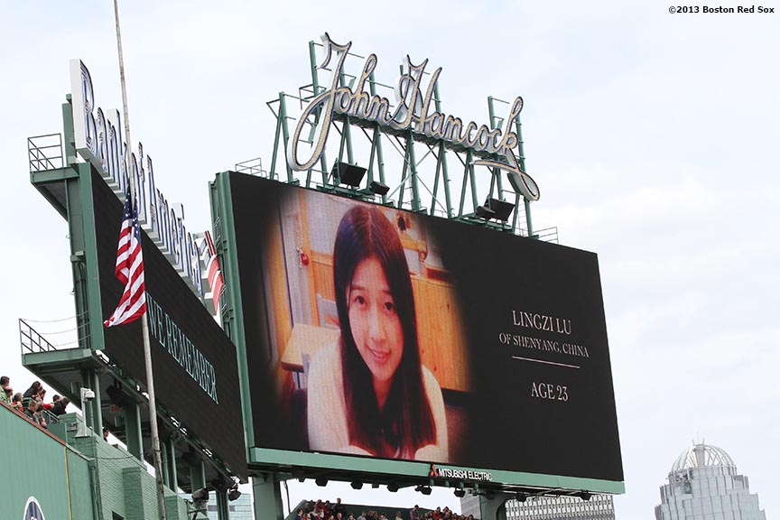 """A picture of Lingzi Lu, one of the victims of the Boston Marathon attacks, is shown on the scoreboard during a pre-game ceremony honoring the victims, first responders, and others involved in the attacks on the 2013 Boston Marathon Saturday, April 20, 2013."""