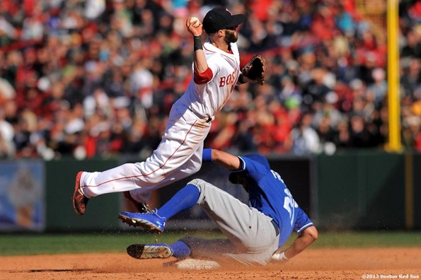 """Boston Red Sox second baseman Dustin Pedroia turns a double play during the eighth inning of a game against the Kansas City Royals Sunday, April 21, 2013 at Fenway Park in Boston, Massachusetts."""