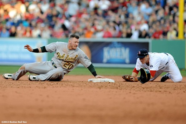 """Boston Red Sox shortstop Stephen Drew applies a tag to Oakland Athletics third baseman Josh Donaldson during the seventh inning Wednesday, April 24, 2013 at Fenway Park in Boston, Massachusetts."""