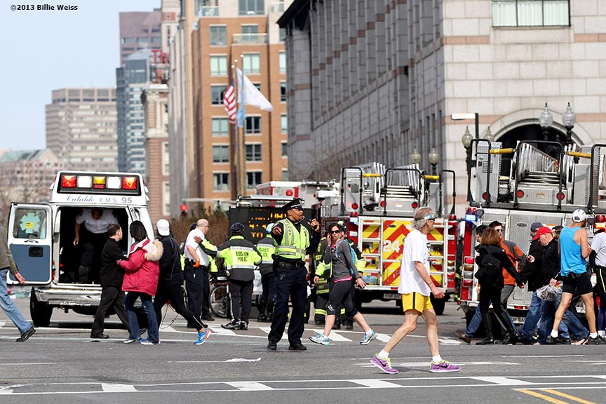April 15, 2013 - Boston, Massachusetts, United States: A member of the Boston Police Department directs pedestrians outside Hynes Convention Center in Copley Square after two bombs were detonated at the finish line of the 2013 Boston Marathon. (Billie Weiss)