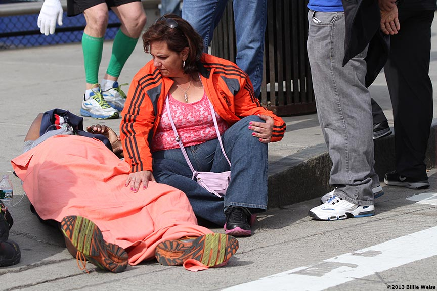 April 15, 2013 - Boston, Massachusetts, United States: A woman cares for a Boston Marathon runner outside Hynes Convention Center after two explosions were detonated at the finish line of the 2013 Boston Marathon. (Billie Weiss)