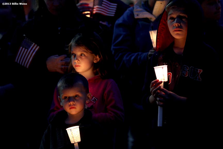 April 16, 2013 - Boston, Massachusetts, United States: From left, Conor Gillis, 4, his sister Emily Gillis, 7, of Dorchester, and their cousin Benjamin McCormick, 8, of Milton hold candles during a candlelight vigil at Garvey Park for Martin Richard, 8, who was killed yesterday in a bomb explosion at the finish line of the 2013 Boston Marathon.(Billie Weiss)