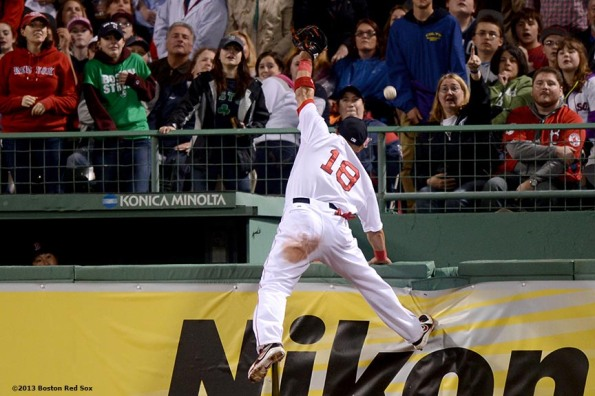 """Boston Red Sox right fielder Shane Victorino climbs the right field wall as he attempts to catch a home run by Minnesota right fielder Oswaldo Arcia during the fourth inning of a game against the Minnesota Twins Thursday, May 9, 2013 at Fenway Park."""