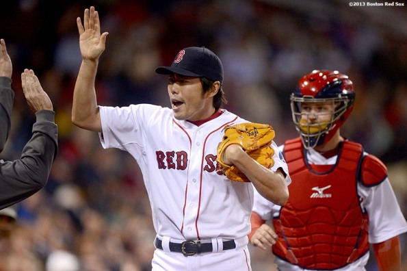 """Boston Red Sox reliever Koji Uehara high fives teammates after retiring the side in order during the eighth inning of a game against the Minnesota Twins Thursday, May 9, 2013 at Fenway Park."""