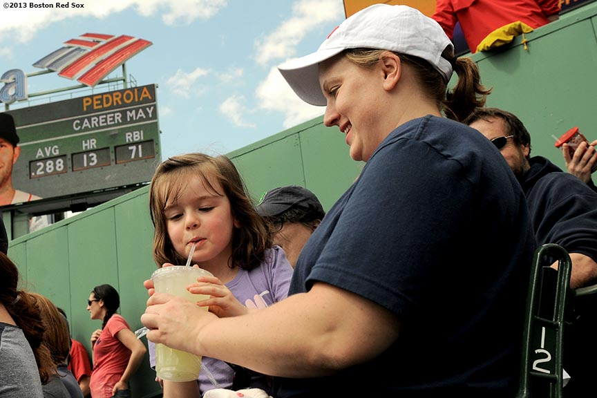 """A young fan in the bleacher seats drinks lemonade as her mother watches during a game between the Boston Red Sox and the Toronto Blue Jays on Mother's Day at Fenway Park Sunday, May 12, 2013 in Boston, Massachusetts."""