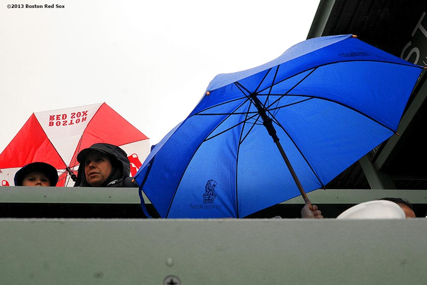 """Fans sit under umbrellas atop the Green Monster during a game between the Boston Red Sox and the Cleveland Indians at Fenway Park in Boston, Massachusetts Saturday, May 25, 2013."""