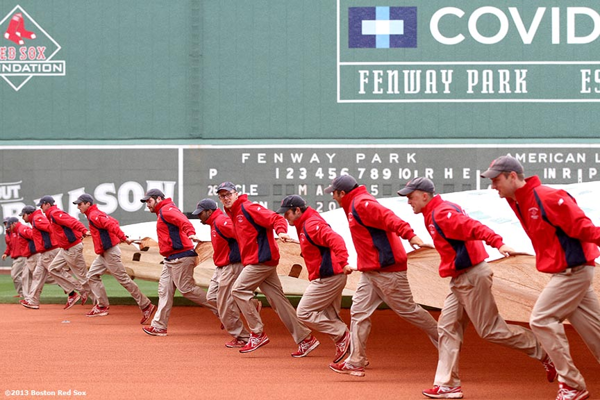 """Members of the Fenway Park Grounds Crew drag a tarp over the infield before a game between the Boston Red Sox and the Cleveland Indians in Boston, Massachusetts Saturday, May 25, 2013."""