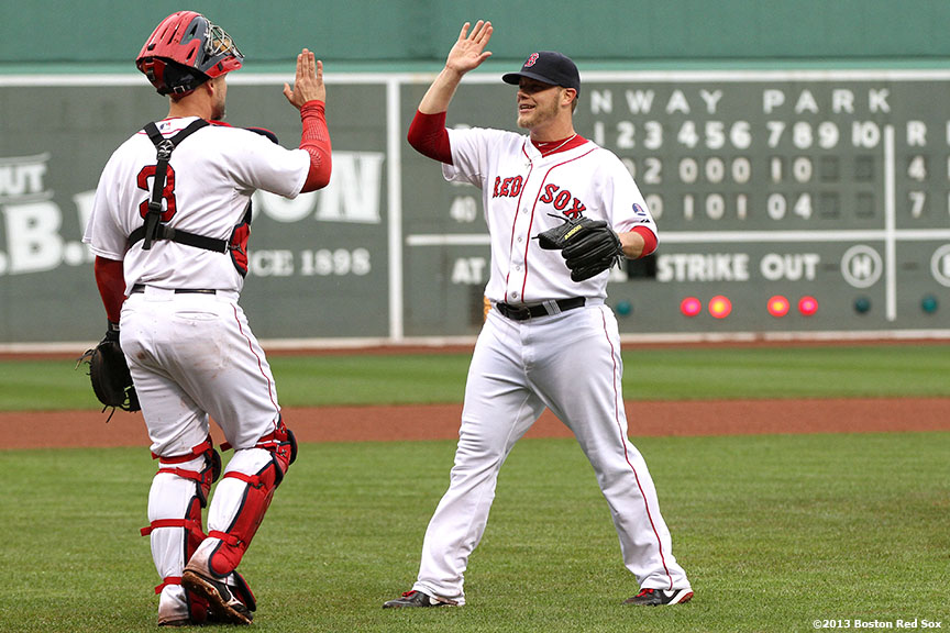 """Boston Red Sox closer Andrew Bailey high fives catcher David Ross after recording a save to defeat the Cleveland Indians 7-4 at Fenway Park in Boston, Massachusetts."""