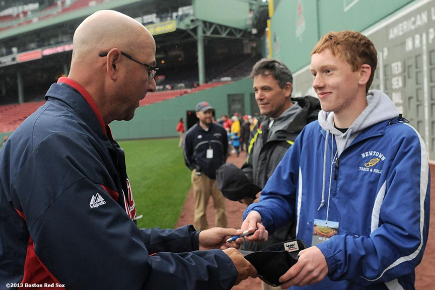 """Former Boston Red Sox and current Cleveland Indians manager, Terry Francona, signs an autograph for a resident of Newtown, Connecticut at Fenway Park in Boston, Massachusetts Saturday, May 25, 2013. The Boston Red Sox recognized Connecticut day by inviting residents of Newtown and members of Sandy Hook Elementary School down to the field to take photos and interact with both Red Sox and Cleveland Indians players and coaches."""