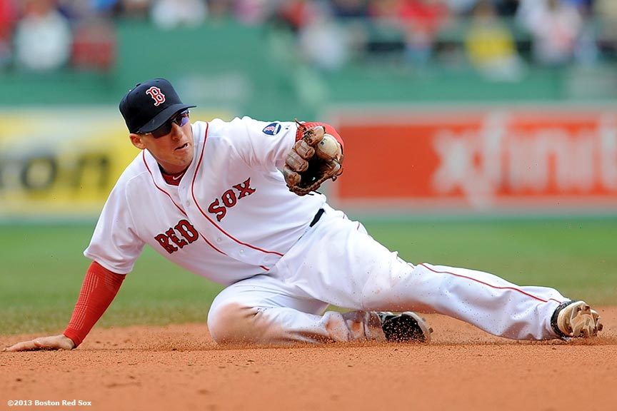 """Boston Red Sox shortstop Stephen Drew makes a diving stop on a ground ball during the ninth inning of a game against the Cleveland Indians at Fenway Park in Boston, Massachusetts Sunday, May 26, 2013."""