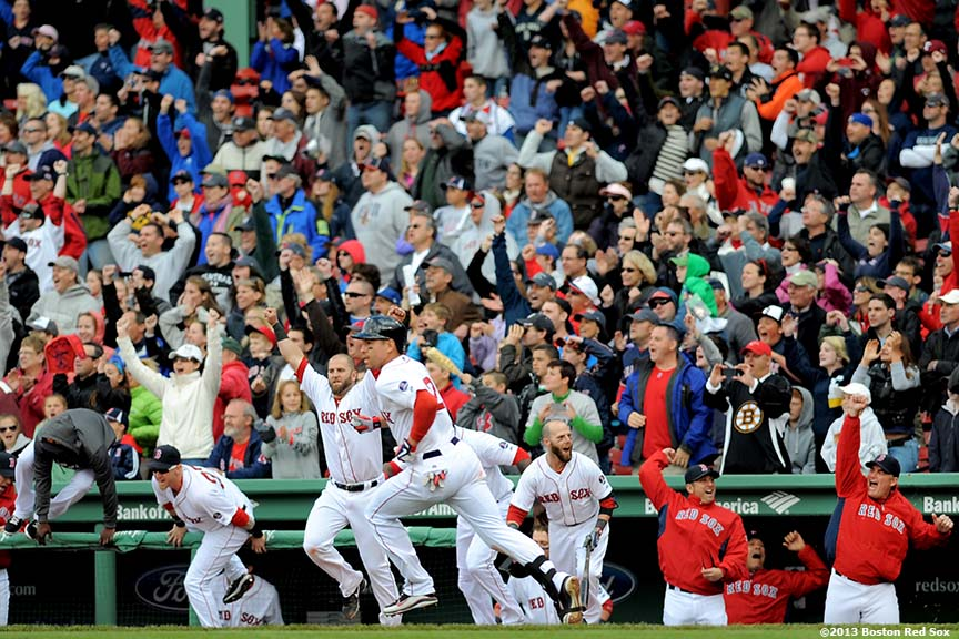 """Members of the Boston Red Sox celebrate as center fielder Jacoby Ellsbury rounds first base after hitting a walk-off single in the bottom of the ninth inning to defeat the Cleveland Indians 6-5 at Fenway Park in Boston, Massachusetts Sunday, May 26, 2013. The Red Sox came back from a 5-1 deficit in the eighth inning."""