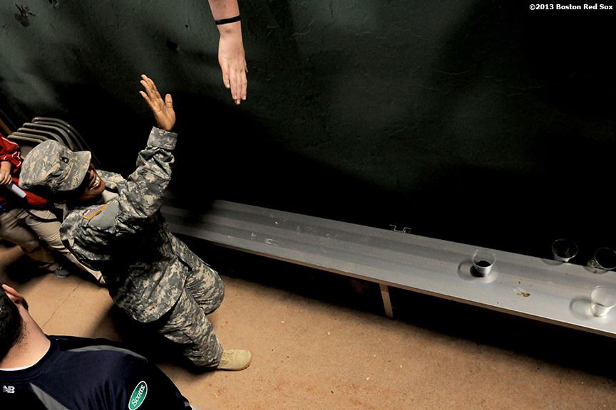 """Sgt. First Class Michelle Lowes of the New Hampshire Army National Guard high fives a fan after singing 'God Bless America' during a game between the Boston Red Sox and the Philadelphia Phillies Monday, May 27, 2013 at Fenway Park in Boston, Massachusetts."""