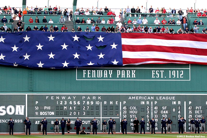 """An American flag is dropped over the Green Monster at Fenway Park in honor of Memorial Day Monday, May 27, 2013 at Fenway Park in Boston, Massachusetts."""