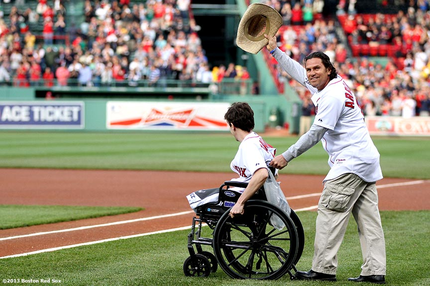 """Jeff Bauman, who lost both of his legs during the Boston Marathon bombings, is wheeled onto the field by Carlos Arredondo, a Marathon spectator who carried Bauman to safety,  before throwing out the ceremonial first pitch before a game between the Boston Red Sox and the Philadelphia Phillies at Fenway Park in Boston, Massachusetts Tuesday, May 28, 2013."""