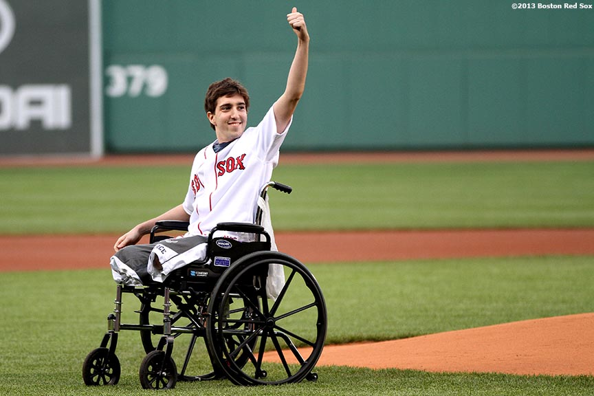"""Jeff Bauman, who lost both of his legs during the Boston Marathon bombings, waves to the crowd before throwing out the ceremonial first pitch before a game between the Boston Red Sox and the Philadelphia Phillies at Fenway Park in Boston, Massachusetts Tuesday, May 28, 2013."""