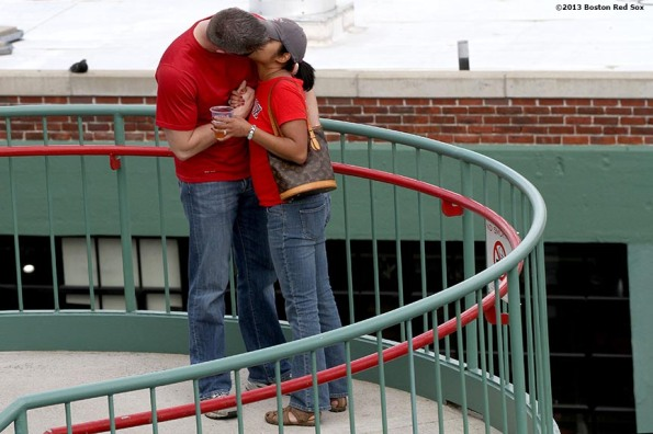 """A couple kisses each other on the stairs inside Gate B during a game between the Boston Red Sox and the Toronto Blue Jays on Mother's Day Sunday, May 12, 2013 at Fenway Park in Boston, Massachusetts."""