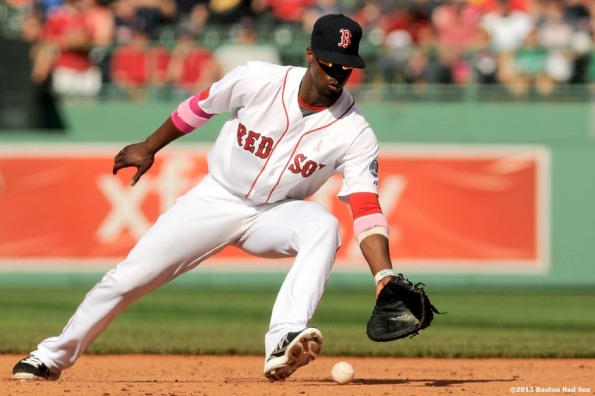 """Boston Red Sox infielder Pedro Ciriaco fields a ground ball at first base during the ninth inning of a game against the Toronto Blue Jays Sunday, May 12, 2013 at Fenway Park in Boston, Massachusetts."""