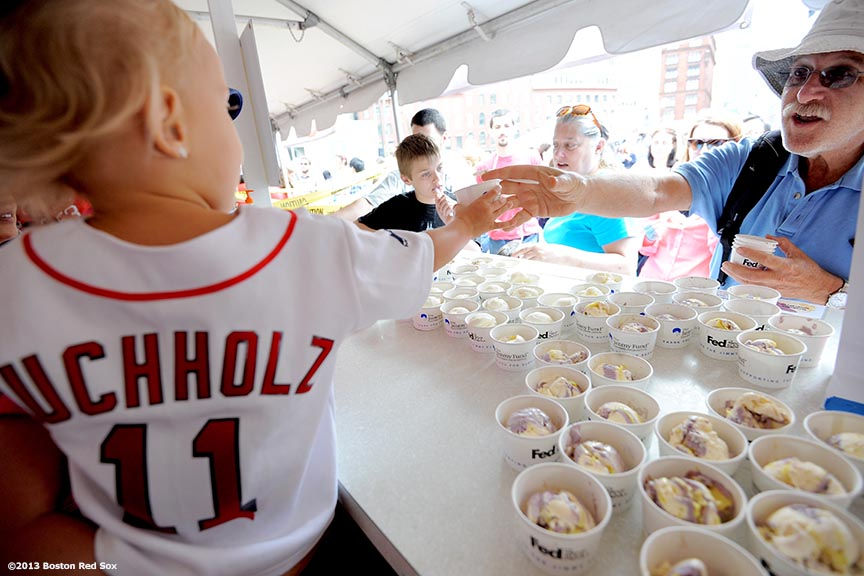 """Coco Buchholz, daughter of Boston Red Sox pitcher Clay Buccholz, hands out ice cream during the 31st annual Jimmy Fund Scooper Bowl, the nation's largest all-you-can eat ice cream festival, at City Hall Plaza in Boston, Massachusetts Tuesday, June 4, 2013. The event has raised over three million dollars for cancer research and care."""