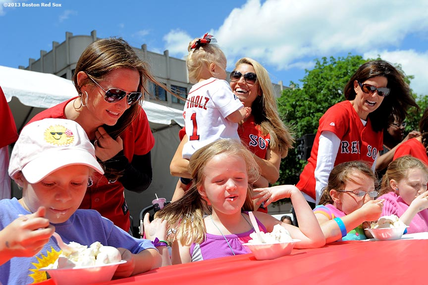 """Boston Red Sox wives cheer as children participate in an ice cream eating contest during the 31st annual Jimmy Fund Scooper Bowl, the nation's largest all-you-can eat ice cream festival, at City Hall Plaza in Boston, Massachusetts Tuesday, June 4, 2013. The event has raised over three million dollars for cancer research and care."""