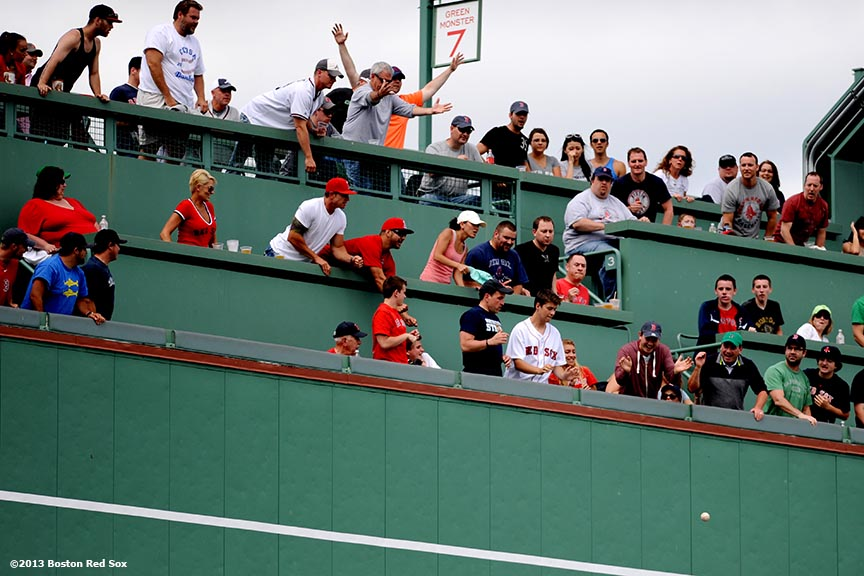 """Fans cheer as a ball bounces off the green monster during a game between the Boston Red Sox and the Los Angeles Angels of Anaheim Saturday, June 8, 2013 at Fenway Park in Boston, Massachusetts."""