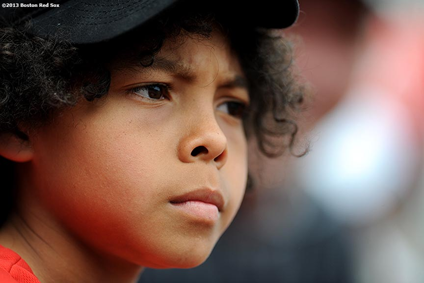 """A young fan watches a game between the Boston Red Sox and the Los Angeles Angels of Anaheim Saturday, June 8, 2013 at Fenway Park in Boston, Massachusetts."""