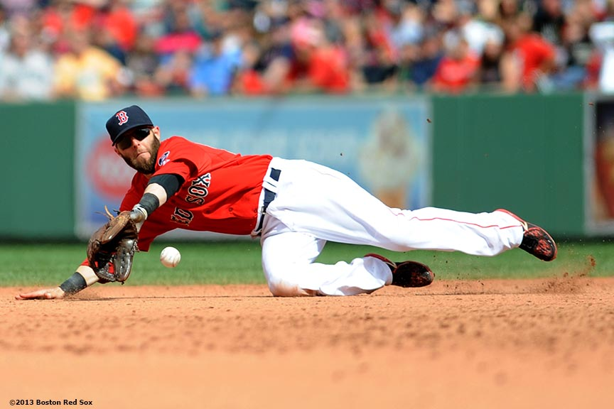 """Boston Red Sox second baseman Dustin Pedroia dives for a ground ball during the seventh inning of a game against the Los Angeles Angels of Anaheim Saturday, June 8, 2013 at Fenway Park in Boston, Massachusetts."""